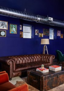 a lounge area of a Chicago apartment building with leather sofa and bookshelves