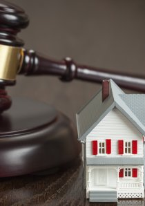 a wooden judge's gavel resting on desk beside model of a house