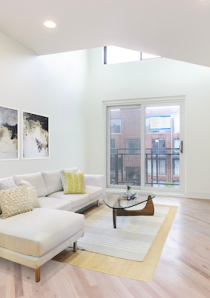 white sofa and glass coffee table in sunlit living room of loft apartment for rent in Chicago