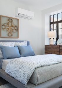 furnished bedroom with A/C unit above bed in Chicago apartment