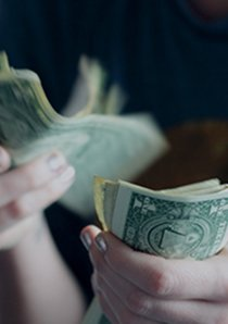 apartment renter counting US dollar bills to make rent payment