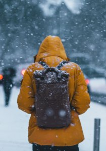 a person wearing a yellow parka and black backpack stands on the sidewalk during a snowstorm