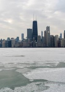 patches of snow and ice float on Lake Michigan with Chicago skyline in background