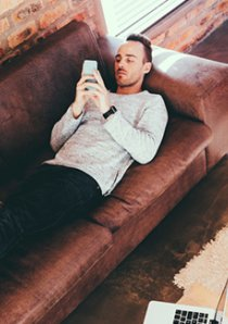 an apartment renter lying on a leather sofa while online shopping with a smartphone