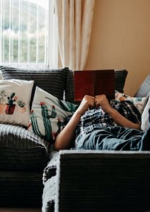 person lying on couch in apartment while reading a book