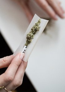 a woman rolling cannabis into a cigarette paper