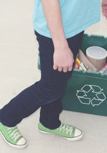 a person dropping a plastic bottle into a green recycling bin
