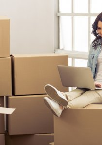 a young woman using a laptop while sitting atop apartment moving boxes