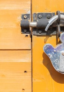 an open steel padlock hangs on a bolt nailed to a yellow wooden door