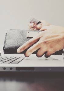a person taking money out of a wallet while using their laptop computer