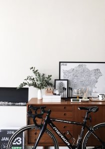 a bicycle leaning against a wooden cabinet in a Chicago apartment