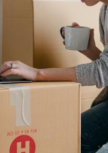 woman using laptop balanced on cardboard moving boxes