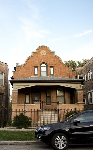 red brick bungalow home with car in front in North Lawndale Chicago