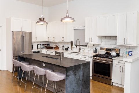 apartment kitchen with black granite kitchen island and white barstools in Chicago apartment for rent