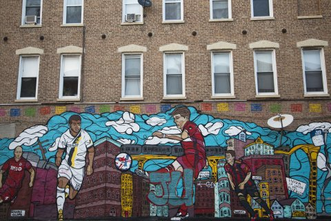 mural on side of apartment building showing MLS Chicago Fire soccer players