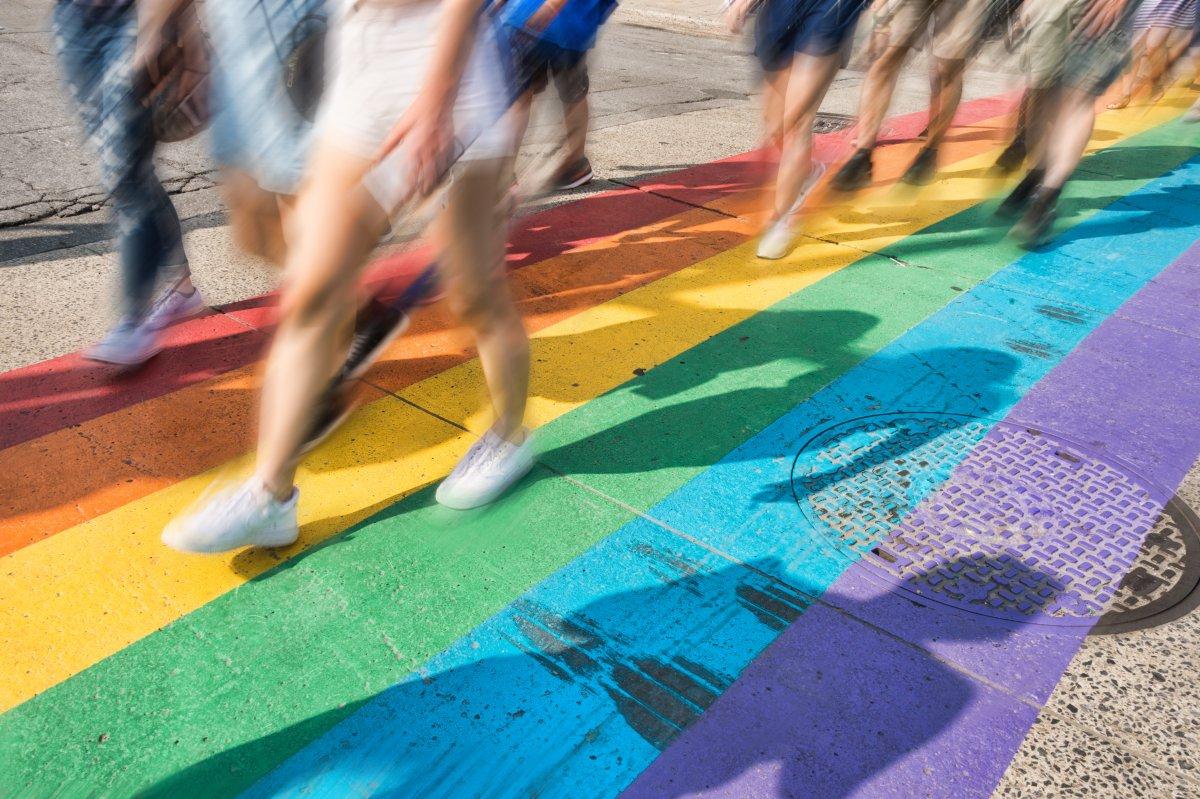 people walking on rainbow painted Pride crosswalk in Boystown Chicago