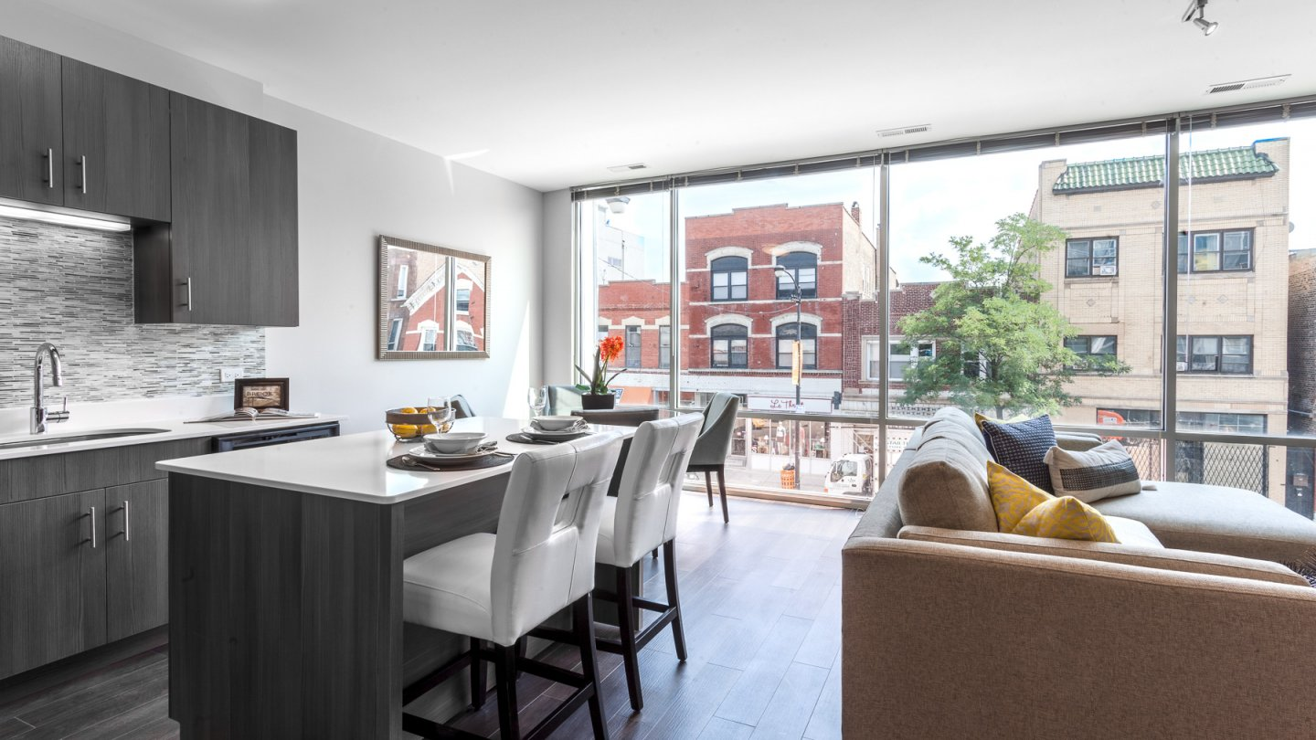 kitchen island with stool and couch at Luxe On Chicago Apartments