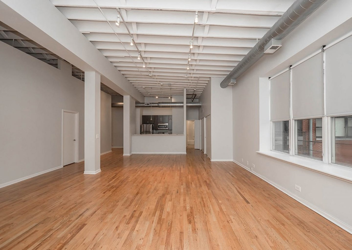 giant loft living room with wood floors at 1550 North Damen Lofts