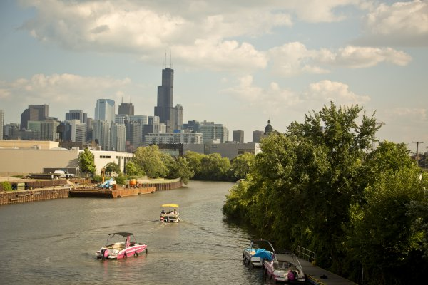 Boats cruising down Chicago River North Branch and Chicago skyline in River West Chicago