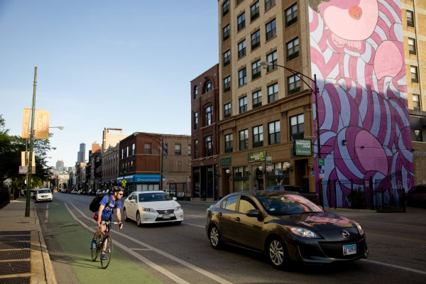 Cyclist riding in bike lane with mural in the background in Noble Square Chicago