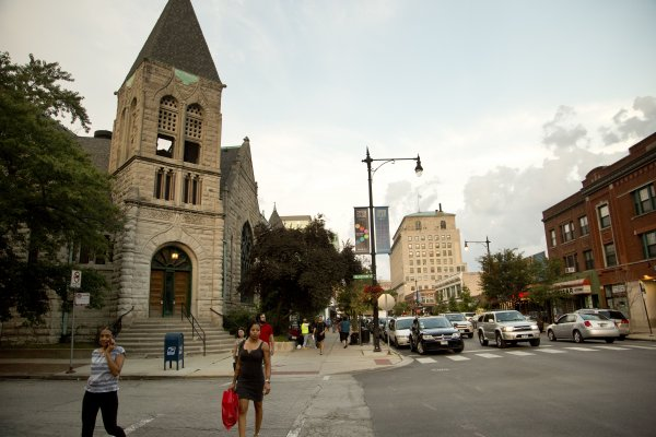Pedestrians crossing 53rd Street and Blackstone Ave with United Church in the background in Hyde Park Chicago