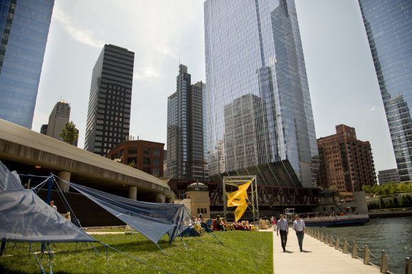 Pedestrians stroll on Chicago Riverwalk next to public artwork in the Loop
