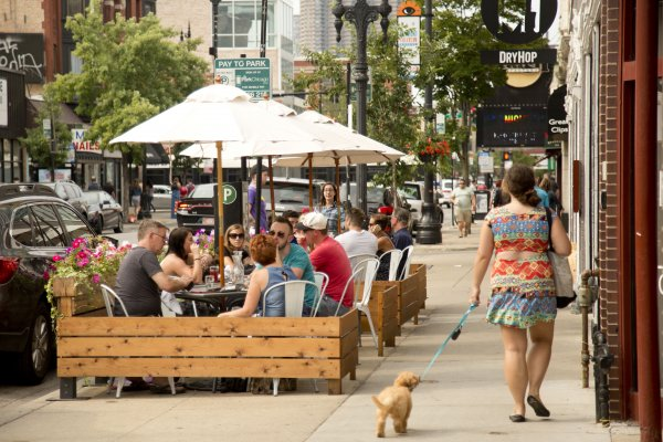 Woman walking dog down sidewalk near restaurant with patio seating in Lakeview Chicago