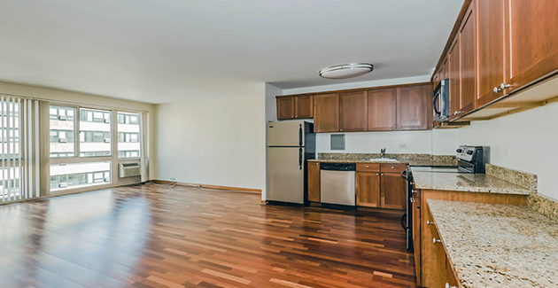 kitchen and living room with cherry hardwood floors in Lakeview apartment for rent at The Van der Rohe in Chicago